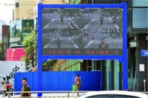 行人闯红灯警示装置正式上岗,如果你闯红灯,就会被拍下留在显示屏上