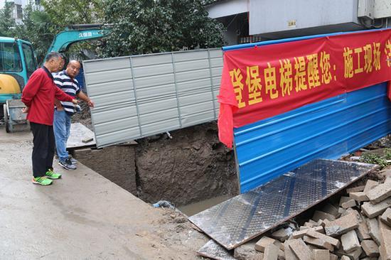 杨老师(红衣者)与施工人员交流。