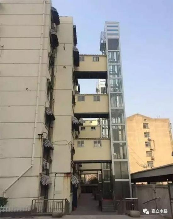"""正在办理相关手续的04幢的电梯效果图,因为楼道紧贴小区道路,电梯只好""""让路"""",建好后上方以通道与楼道相连。"""