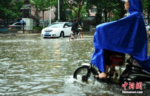 7月16日,河北石家庄一条马路积水严重,民众涉水骑行。当日,该省气象台发布暴雨蓝色预警,多地遭受暴雨袭击。中新社记者 翟羽佳 摄