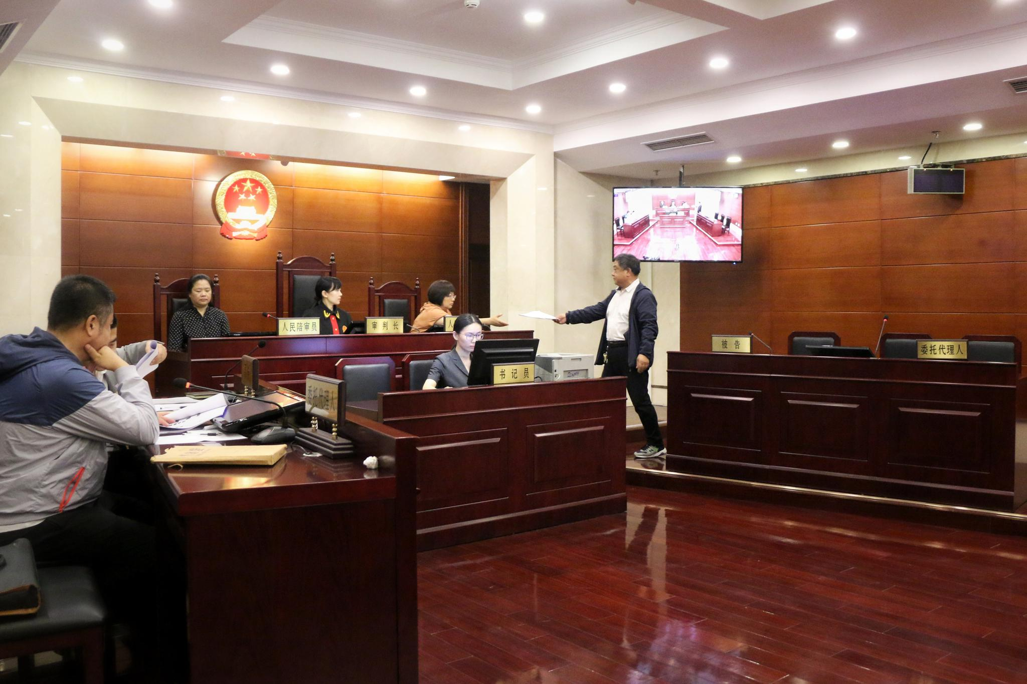 被告委托代理人庭上向审判长提交证据。实习生 陈婉婷 摄