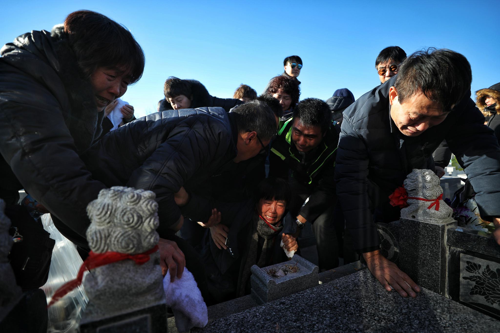 2018年12月13日,天津市宁河区永定塔陵,张洁父亲用手擦拭墓碑,众人搀扶伤心的张母亲。 新京报记者 王飞 摄