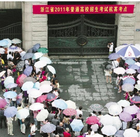 2011年高考首日下暴雨,考点外都是打伞的家长,十分壮观。 本报记者 吴煌 摄