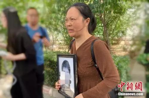 谢雕母亲带着谢雕的遗照走出法院中新网杨雨奇 摄
