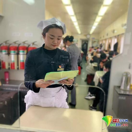 餐车长崔莉正在对着配料单和厨师沟通。