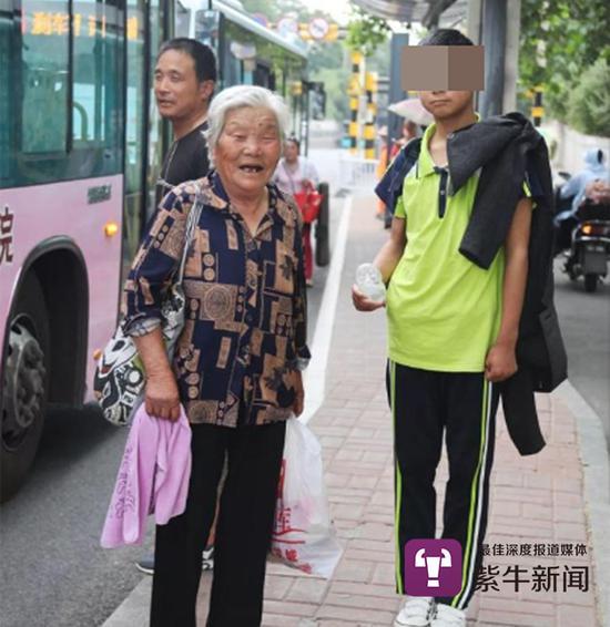 祖孙俩在等待回家的公交车(吕品摄)
