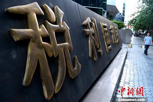 市民从税收宣传标语旁经过。(资料图片)中新社记者 张斌 摄