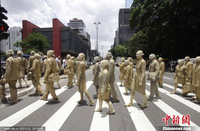 资料图:巴西圣保罗,几十名身穿职业装、涂满黄泥的蒙面人走上街头,呼吁人们关注都市上班族的工作压力。图片来源:CFP视觉中国
