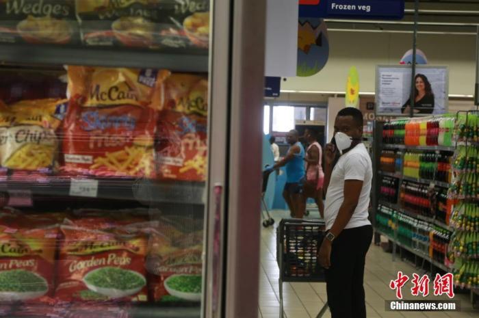 """当地时间4日1日,南非约翰内斯堡,当地民众佩戴口罩在超市内选购冷冻食品。受疫情影响,南非已经实施全国范围""""封城""""。中新社记者 王曦 摄"""