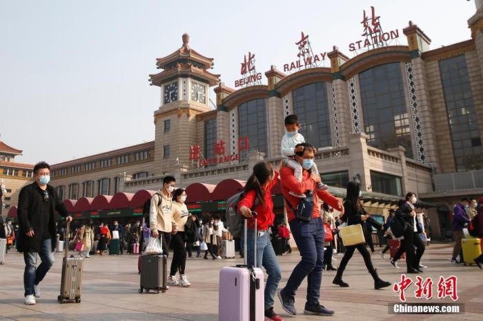 10月7日,旅客走过北京火车站广场。中秋国庆假期即将结束,北京站客流渐增。