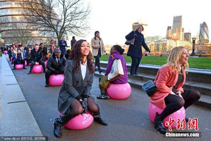 资料图:英国伦敦,超过100名通勤者早间利用充气跳跳球行进。