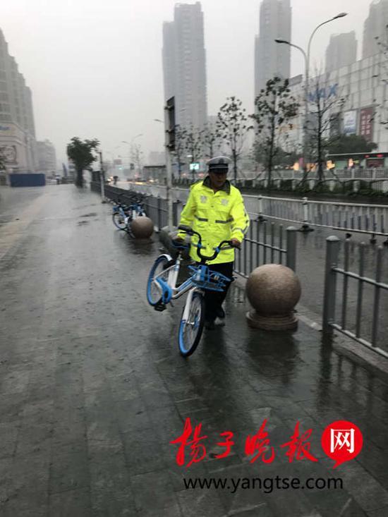 民警雨中抬车。