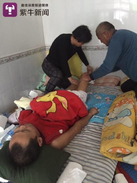 老人们在照顾躺在床上的陈岗