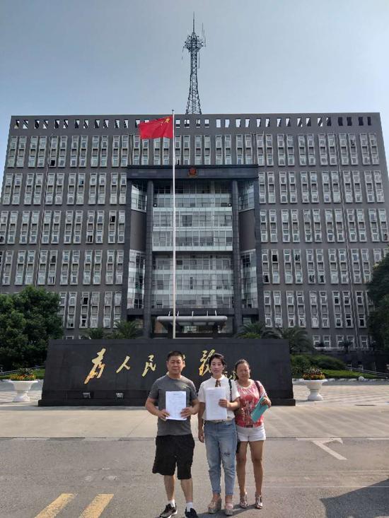 6月21日,王彬如拿到判决书后,摄于法院门口。受访者供图。