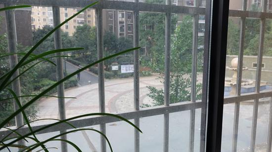 从周菊梅家阳台可以清楚看到小区广场,相距仅几米远。