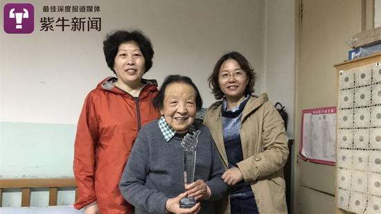社区领导给朱奶奶颁发奖杯