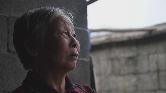 李尚平的母亲王玲秀坐在院子里。新京报