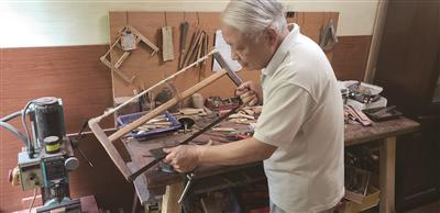 陈和生老人在工具台制作模型。
