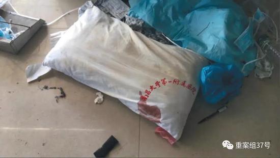 11月29日,顺达洗涤服务中心内,一个带血的枕头被工人扔在地上的垃圾堆里等待洗涤,旁边还堆放了医生手术帽和输液管等医疗废物。 新京报记者 尹亚飞 摄