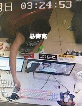 拍下嫌疑人在网吧偷窃手机。视频监控截图