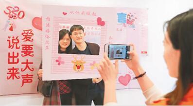 """每年的5月20日都是情侣结婚登记的热门日子之一。图为2019年5月20日,在重庆市沙坪坝区民政局婚姻登记处,新人在""""说出爱的誓言""""环节合影留念。孙凯芳摄(人民视觉)"""