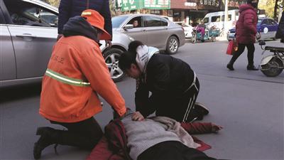 刘小琴和小姑娘轮流给倒地男子做心肺复苏。