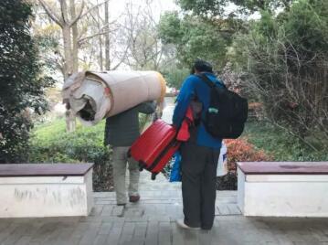 ▲被劝离后,农民工们将行李从墓园搬走。