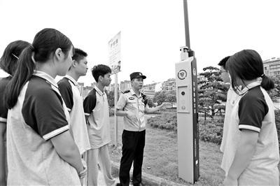民警在给学生讲解如何使用一键报警柱。