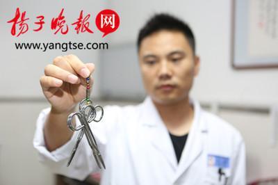 将这些磁铁连在一起可以吸起三把手术剪刀。刘威 摄