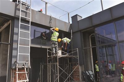 工人在进行试验性拆除,卸下内侧玻璃测试施工方案。