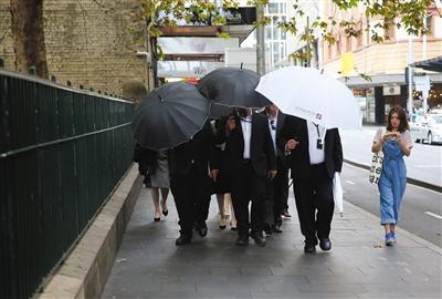 高云翔的妻子董璇昨天参加庭审,躲避在保镖的黑伞之后。 图/视觉中国