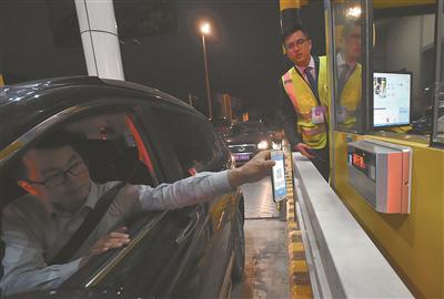 """一位司机在宿扬高速扬州段蜀冈收费站出口,通过""""扫码""""付费。 庄文斌 张震宇摄"""