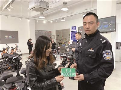 """曾女士成为新国标实施首日南京电动车上牌第一人,领到""""苏AA000718""""车牌。"""