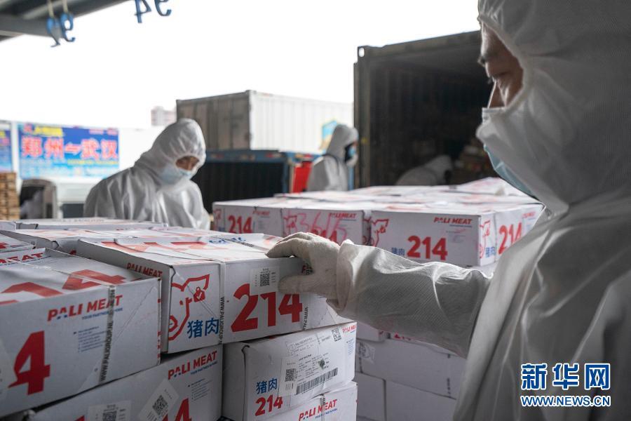 """1月7日,在武汉万吨·华中冷链港,工作人员对进口冷链食品贴上用以溯源的""""鄂冷链""""码。"""