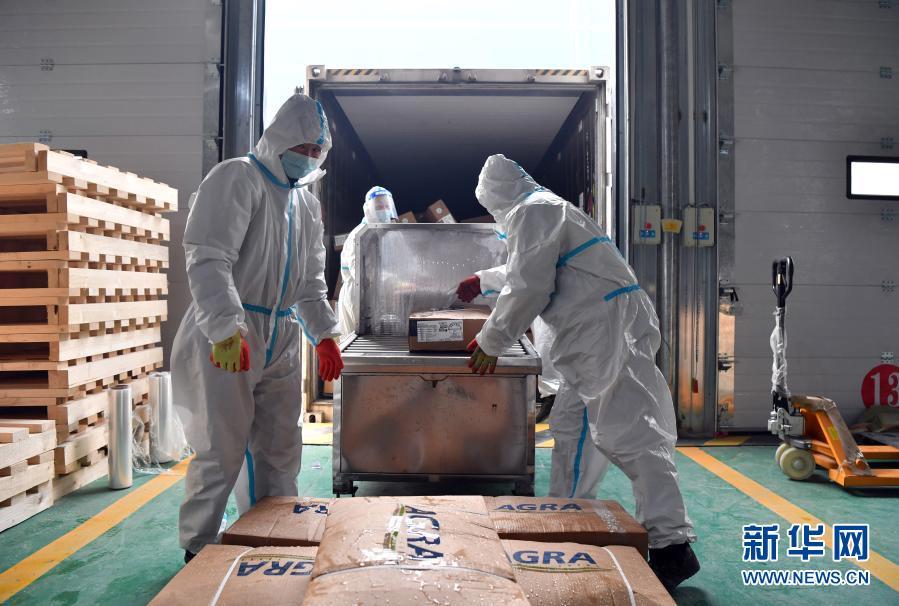 1月22日,在郑州市进口冷链食品集中监管仓(惠济仓),工作人员将消毒的进口冷链食品放置在货架上。