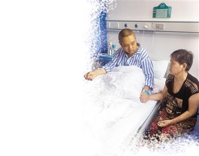 手术前,王俊的妈妈守在他的病床边,紧紧攥着他的手。 本报记者 纪文伶 摄