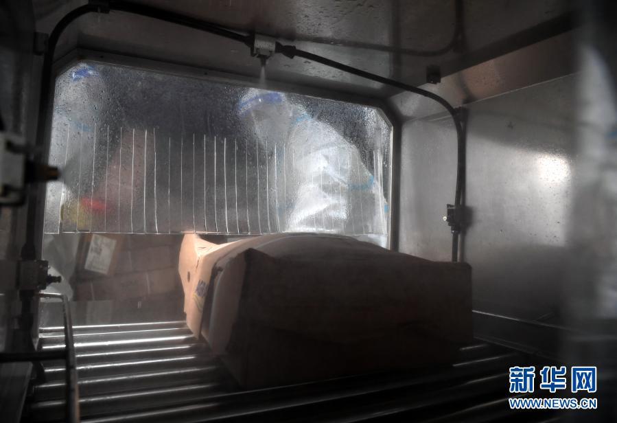 1月22日,在郑州市进口冷链食品集中监管仓(惠济仓),工作人员将进口冷链食品放入自动消毒机。