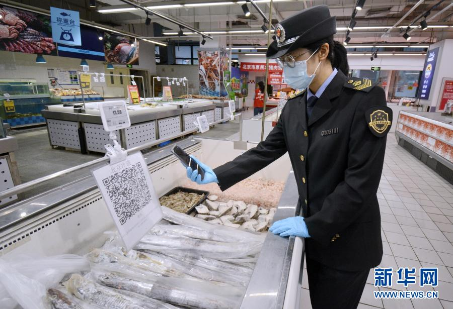 北京市丰台区市场监督管理局东高地街道市场监管所的执法人员在核查超市内的进口冷冻食品追溯信息(2020年11月3日摄)。