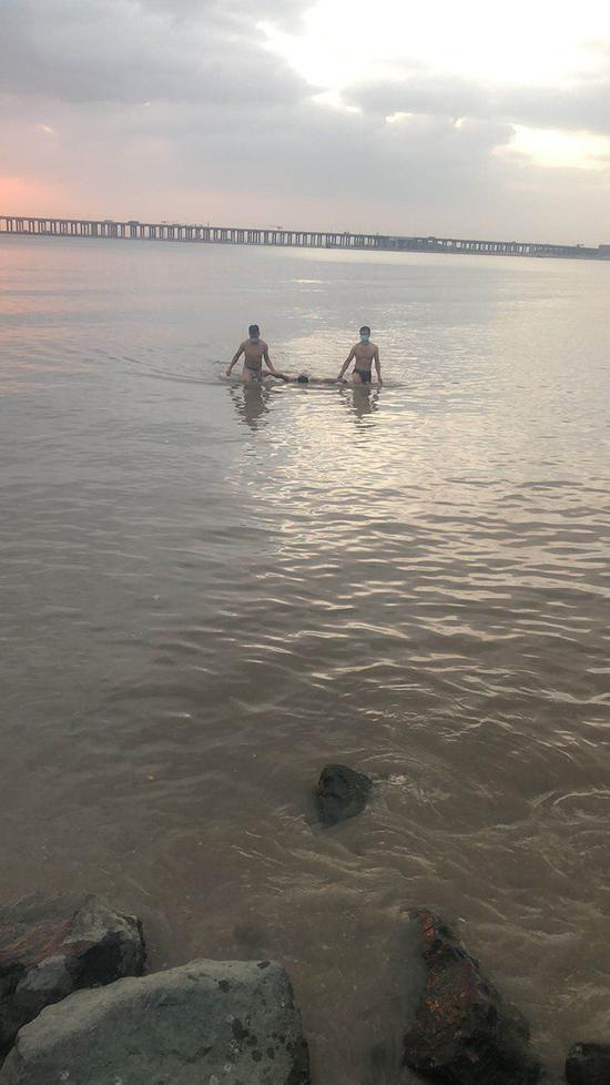 两名协警下海将男子救上岸。