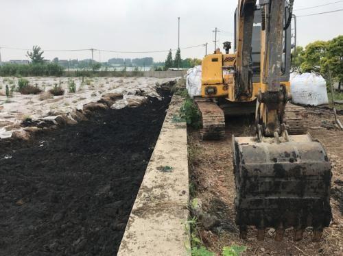 污泥池边停放的小型挖掘机。图片来源:生态环境部网站。