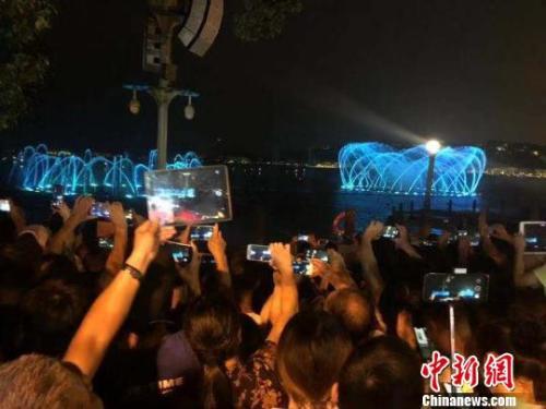 游客用手机记录下音乐喷泉的美丽瞬间