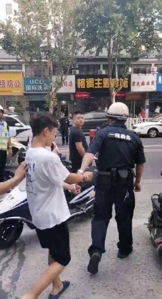 图砍人:酒后持刀砍人的行凶男子被警方带走调查。(网友供图)
