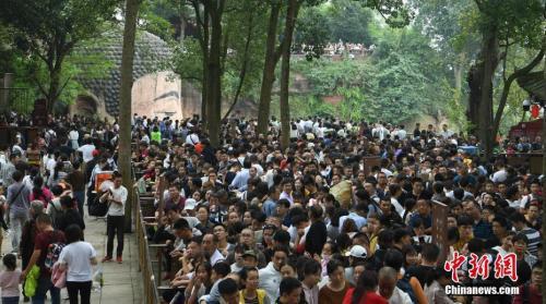 10月3日,四川乐山,游客排队下栈道观大佛。当日,乐山大佛景区迎来国庆长假客流高峰,景区内游人如织。