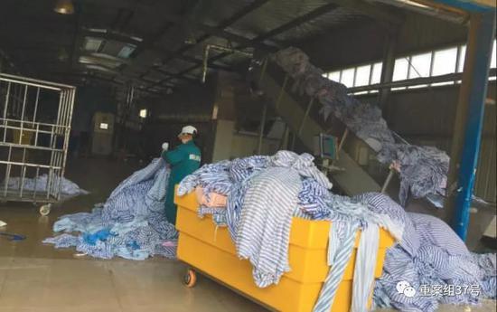 11月28日上午,顺达洗涤服务中心内,一名工人正将从医院收来的布草进行拆分,工作人员在拆分时,直接踩在布草堆里工作。 新京报记者 尹亚飞 摄