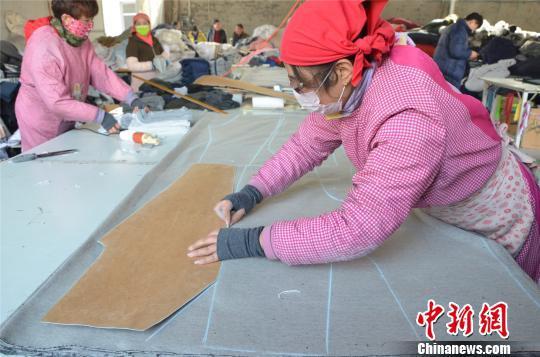 图为姚家坡村村民正在划线、裁布。 郝学娟 摄