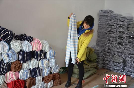 图为姚家坡村村民展示其生产的秋裤。 郝学娟 摄
