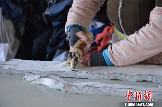图为姚家坡村村民正在裁布、制作秋裤。 郝学娟 摄