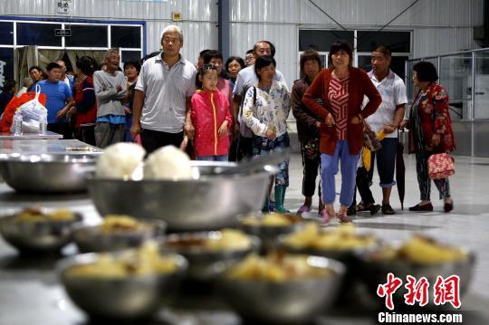 在山东寿光集中安置点,民众有序排队领取馒头、蔬菜等食物,一日三餐得到保障。 梁犇 摄