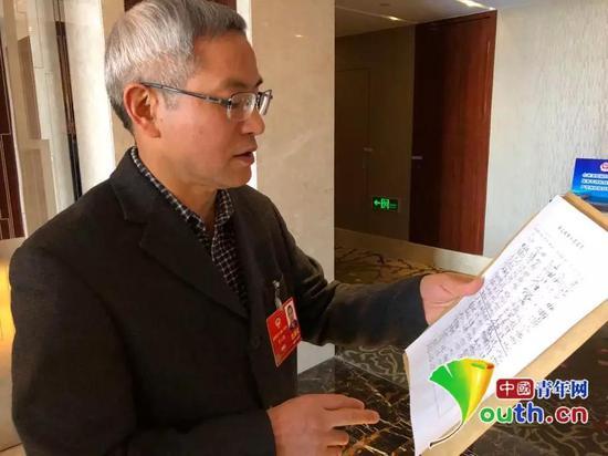 全国政协委员贺云翱发起这份联合提案,图为提案最终递交前他向记者介绍签名情况。中国青年网记者 吴楚 摄