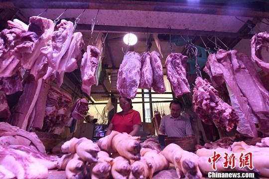 重庆主城区的一家农贸市场内,商贩正在摆放猪肉。